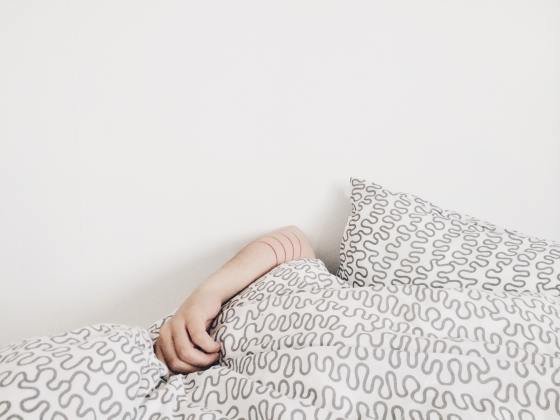 an arm peeking out of a fluffy duvet in bed